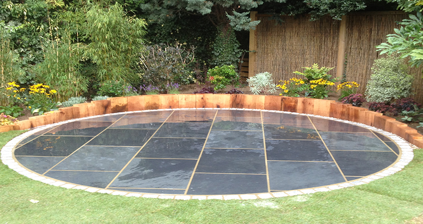 Brazilian black slate circular patio with silver grey granite cobbles and vertical oak sleeper retaining edge. Sevenoaks, Kent