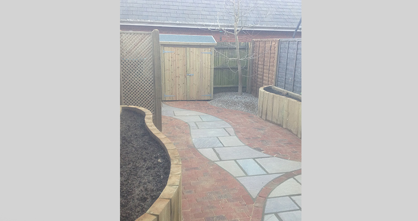 Courtyard garden brick paved with meandering Indian stone pathway. Larkfield, Kent