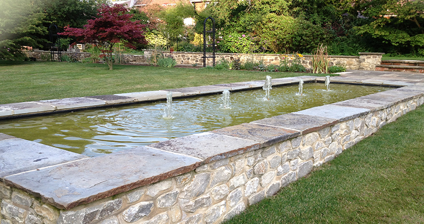 Formal raised ornamental pond with water fountains. Bitchet Green, Seveonaks, Kent