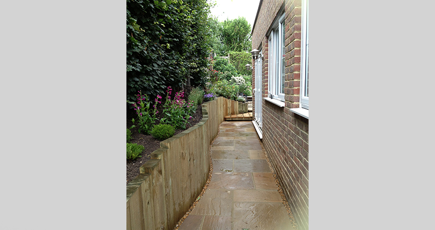 Indian sand stone side pathway with sleeper retaining wall. Ightham, Kent