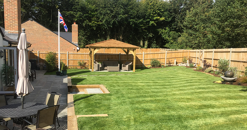 Lawn with sleeper retaining wall in Addington, Kent