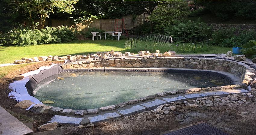 Mid construction of Rag Stone walling surrounding a pond in Sevenoaks, Kent