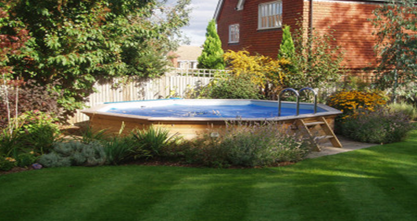 Natural planting to soften the pool surround using shrubs summer flowers. Plaxtol, Kent