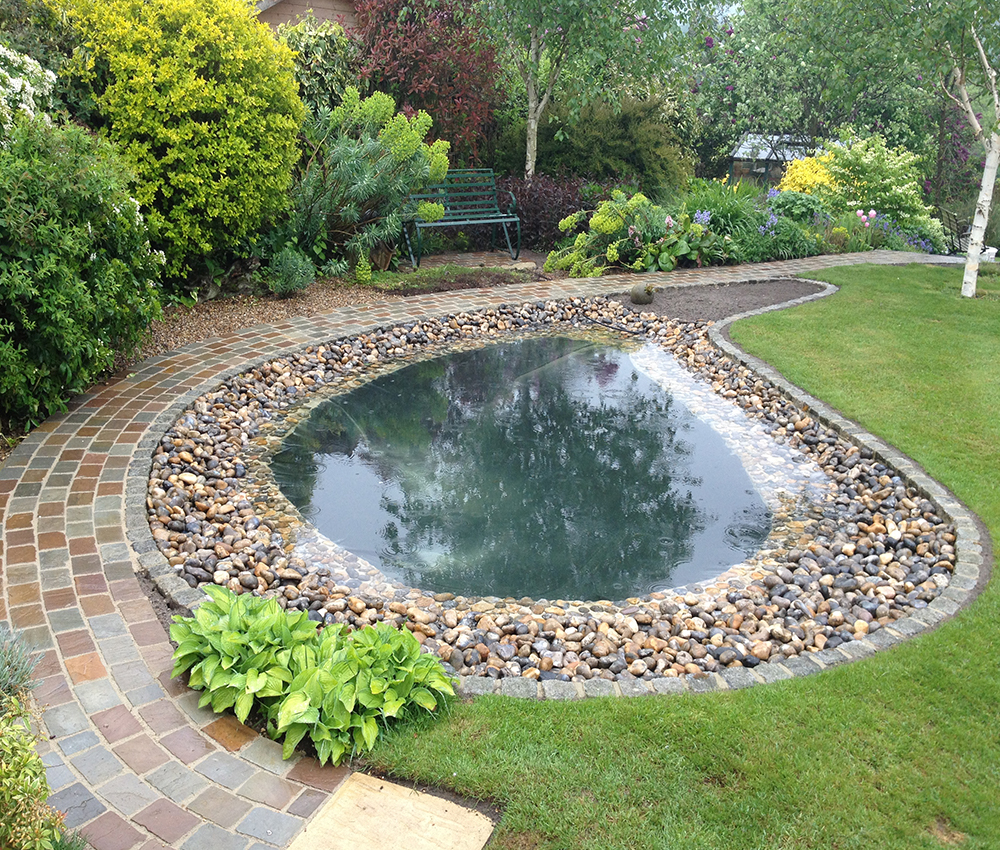 Ornamental pond with a softened natural pebble surround Ightham Kent