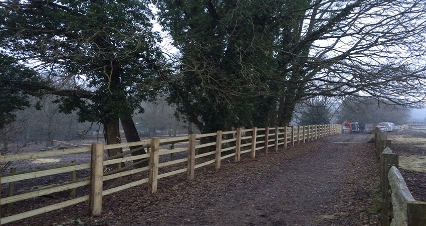 Post and rail fencing along field track at riding school. Ightham, Sevenoaks, Kent