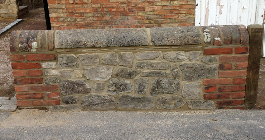 Rag stone wall restoration with Kent Reds brick piers and stone capping. Wrotham, Sevenoaks, Kent