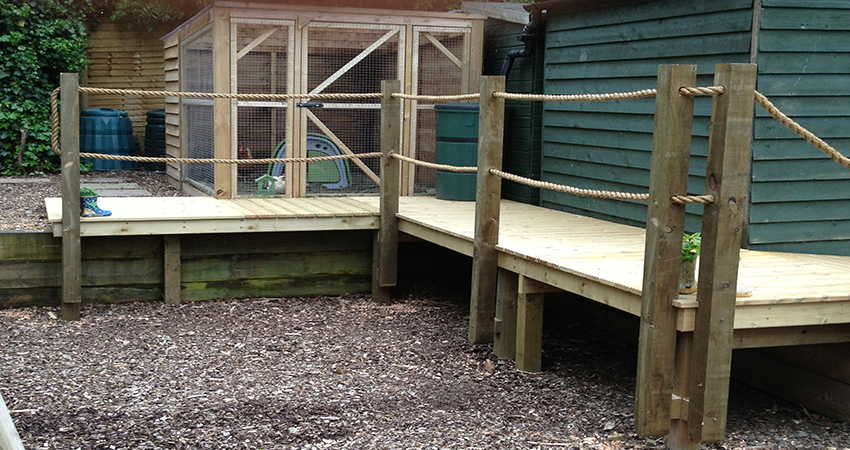Raised boardwalk with rope handrail leading to chicken run. Kemsing, Kent