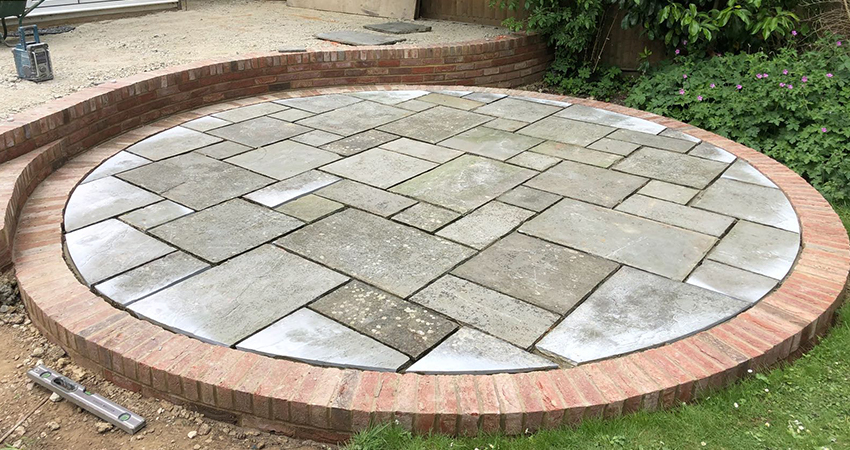 Raised circular indian sand stone patio with brick surround. Sevenoaks, Kent
