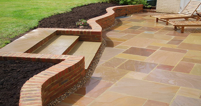 Raj Indian stone paving with central step to main lawn. South Godstone, Surrey