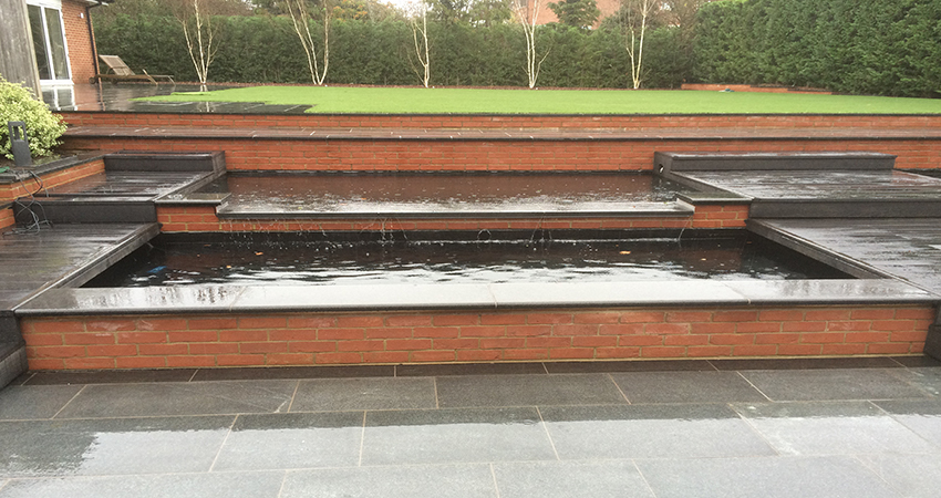 Terraced Koi ponds with water blade feature using Granite stone and composite decking.