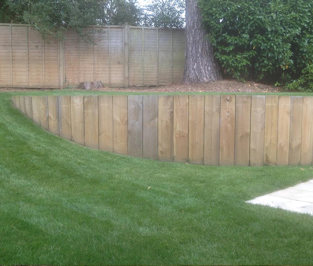 Vertical sleeper retaining wall in rear garden lawn Sevenoaks Kent